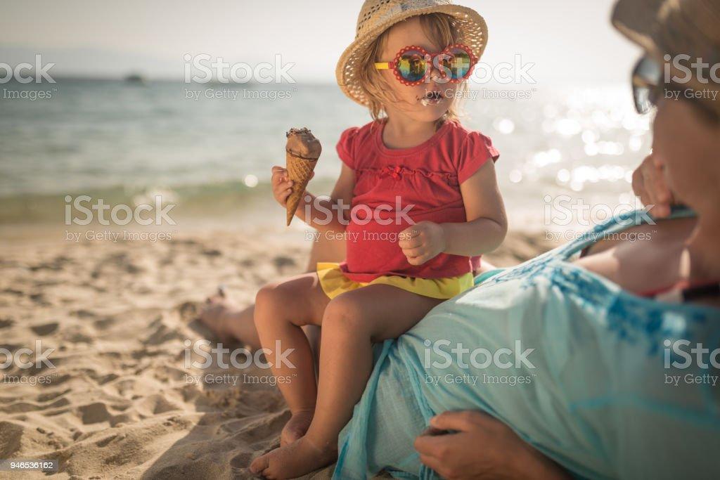 Kleines Mädchen mit Mutter am Sandstrand essen Eis Sitzgelegenheiten – Foto