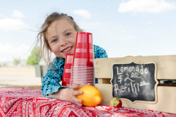 Little girl selling drinks at lemonade stand A little girl selling lemonade reaches for a lemon and smiles. Sign indicates price of drinks. lemonade stand stock pictures, royalty-free photos & images