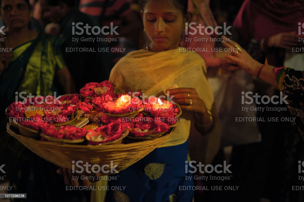 A little girl selling floating diyas decorated with flower at the ghats of Varanasi just before evening 'aarti' ritual royalty-free stock photo