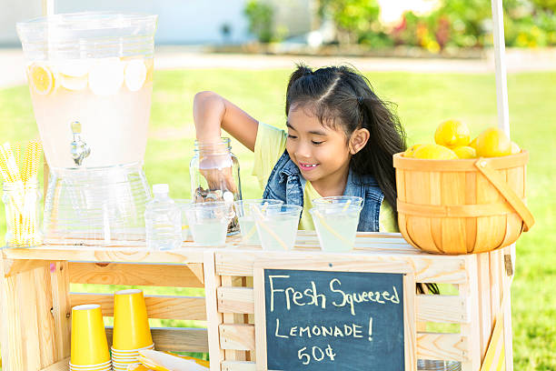 Little girl sells lemonade in her front yard Happy girl makes fresh lemonade to sell at lemonade stand in her front yard. A basket of lemons and a beverage dispenser are on the stand. lemonade stand stock pictures, royalty-free photos & images