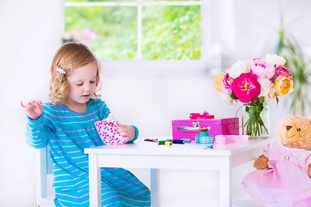 kleines mädchen nähen ein kleid für ihre puppe - nähpuppen stock-fotos und bilder