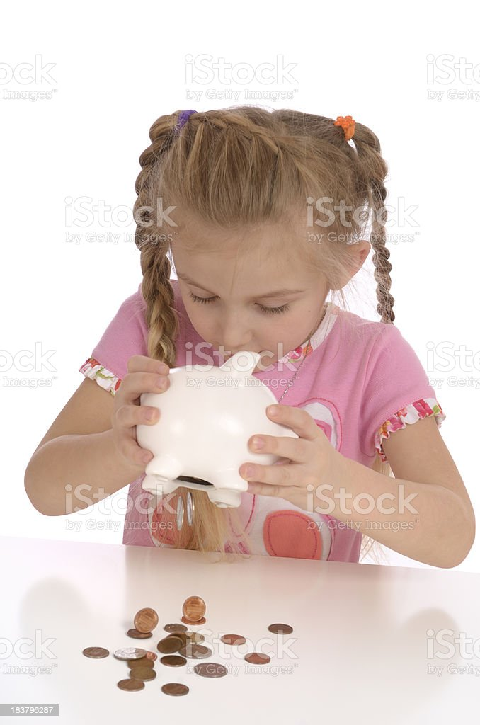 Little girl shaking coins from piggy bank royalty-free stock photo