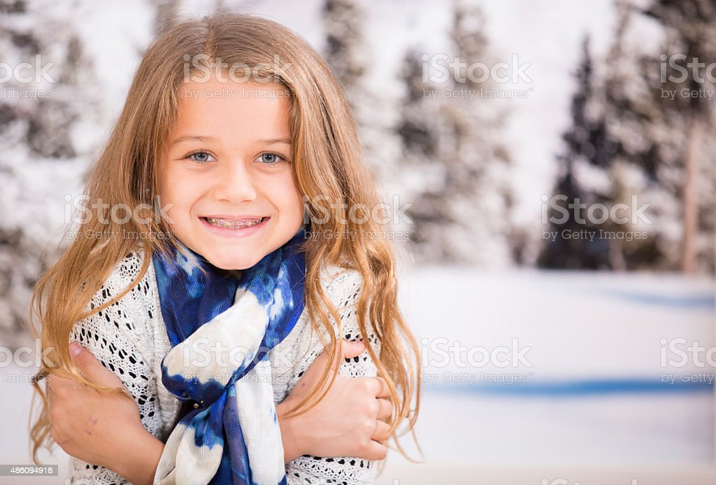Little girl shivering in the winter snow. Outdoors. stock photo