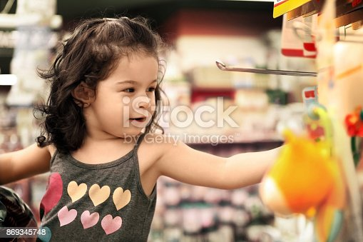 926078666 istock photo Little girl shopping at supermarket 869345748