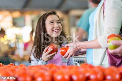 Elementary age Hispanic little girl is smiling while shopping for fresh produce at market or local grocery store with her mother. Child is holding a ripe red tomato in produce section and smiling while looking up at her mom.