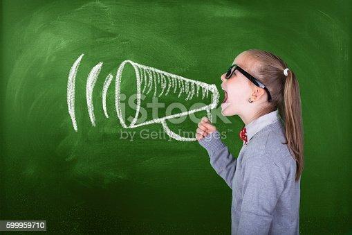 991060890 istock photo Little girl shouting on megaphone in front of green blackboard 599959710