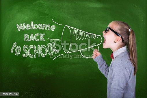 991060890 istock photo Little girl shouting on megaphone in front of green blackboard 599959732