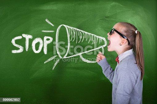 991060890 istock photo Little girl shouting on megaphone in front of green blackboard 599962852
