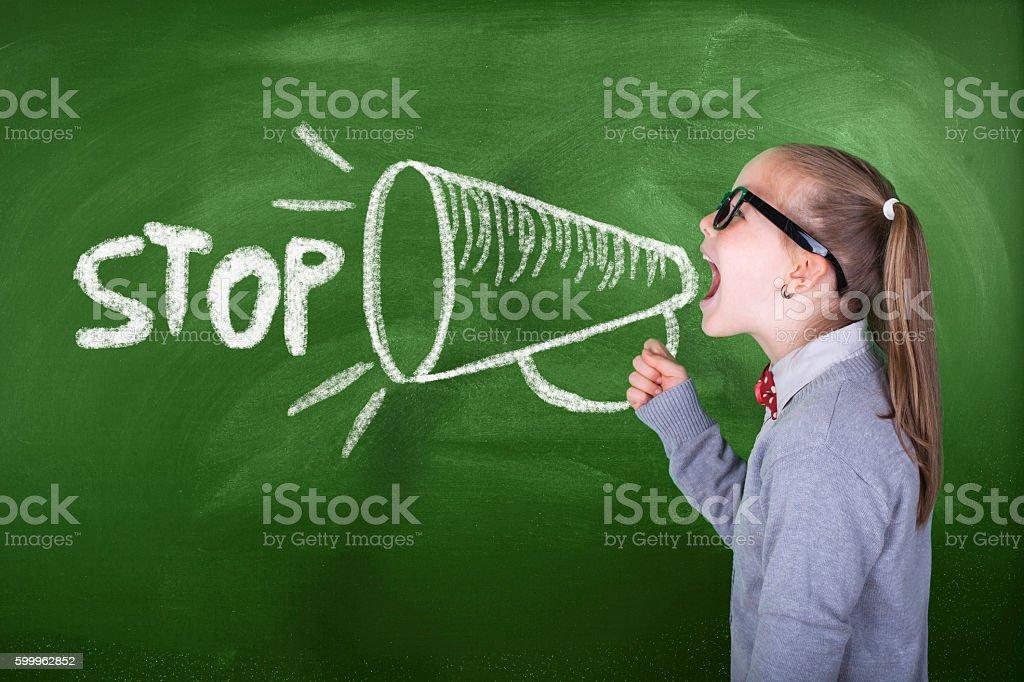 Little girl shouting on megaphone in front of green blackboard stock photo