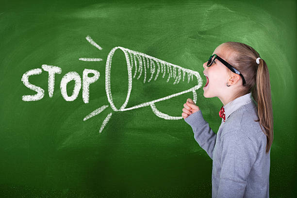 Little girl shouting on megaphone in front of green blackboard stock photo