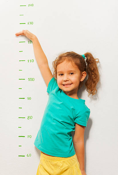 kleine mädchen zeigen, wie hoch sie werden bald - wachstumstabelle baby stock-fotos und bilder