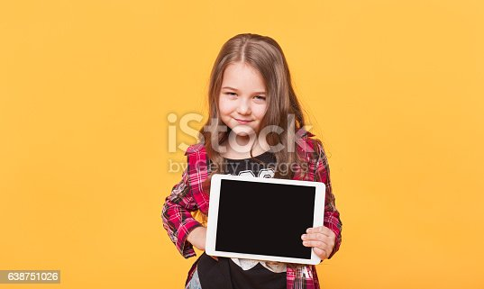 istock little girl showing blank black tablet pc on yellow background 638751026
