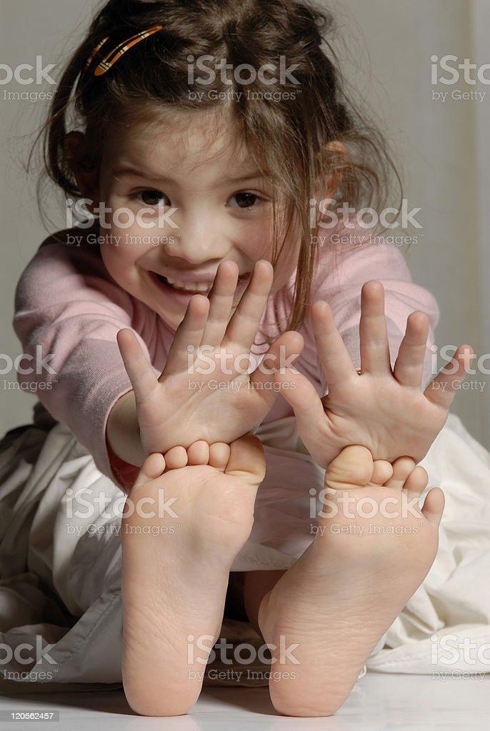 Little girl showing her hands and feet stock photo