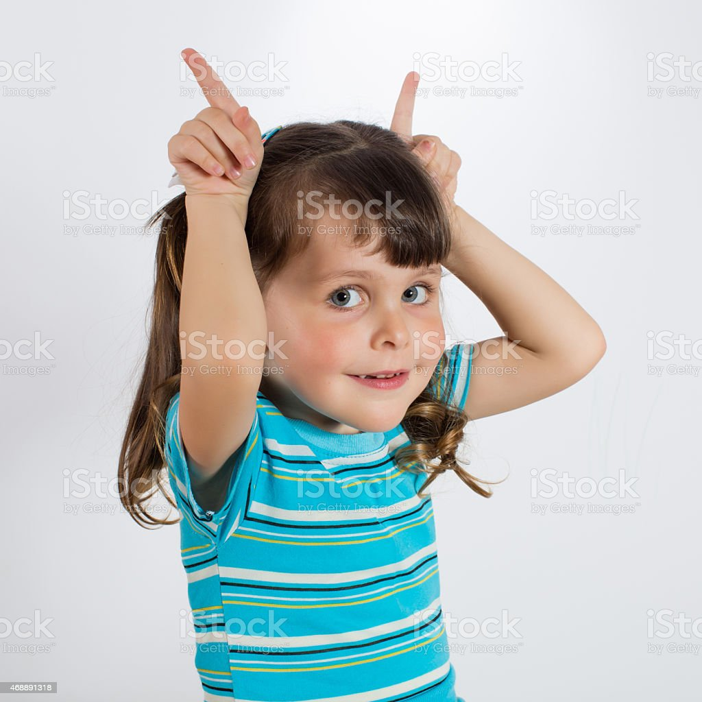 Little girl showing rabbit ears stock photo