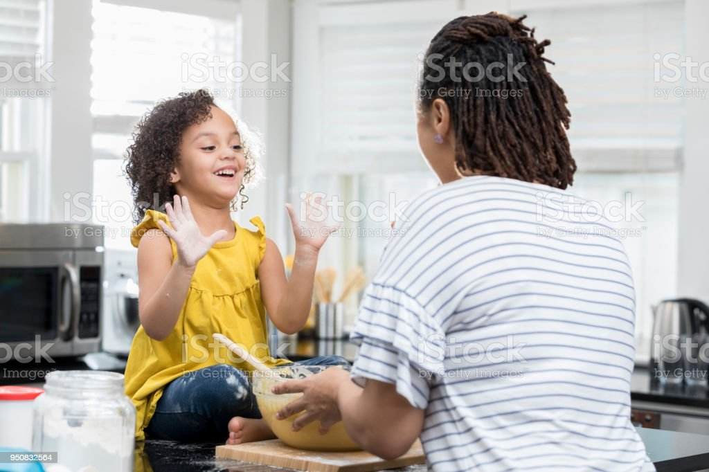 Cute mixed race girl shows her mom her messy hands while baking a...