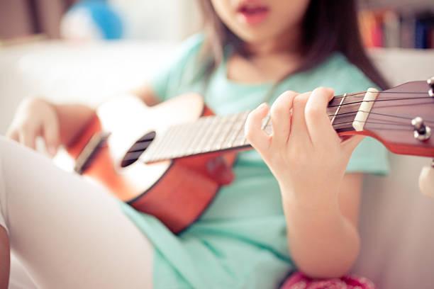 kleines mädchen singt und spielt auf couch ukulele - ukulele songs stock-fotos und bilder