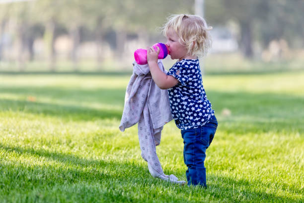 Little Girl Sips on Her Sippy Cup While Holding Her Blanket in a Park stock photo
