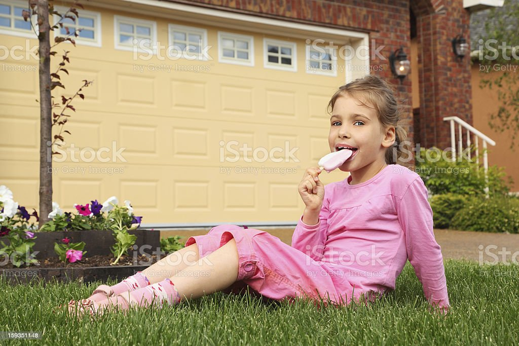 Little girl sits near cottage and eats ice cream. royalty-free stock photo