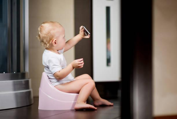 niña se sienta en una olla en el baño y toma un selfie en un teléfono inteligente - foto de stock