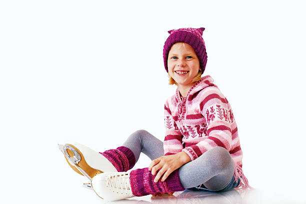 Little girl sits on the ice in ice skating. stock photo