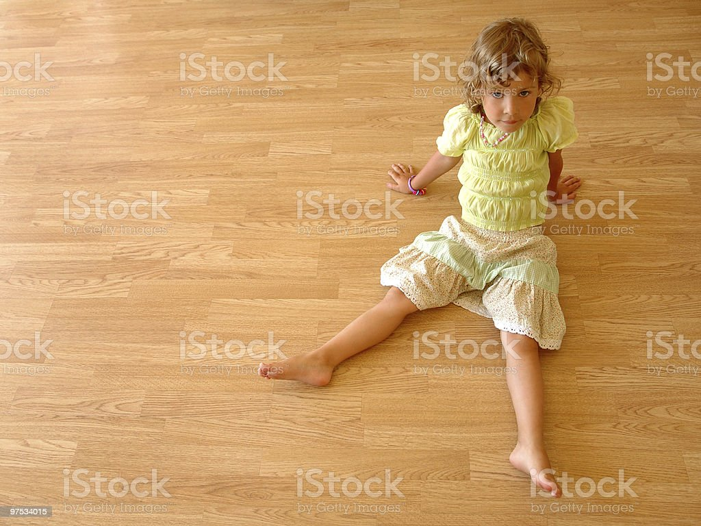 Little girl sits on wooden floor royalty-free stock photo
