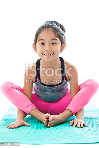 Little Girl Sits With Feet Together On Yoga Mat Stock