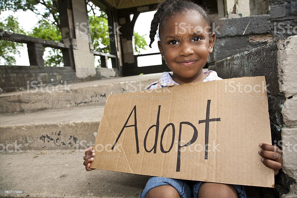 Little Girl Sitting and Holding Cardboard Sign Saying Adopt royalty-free stock photo