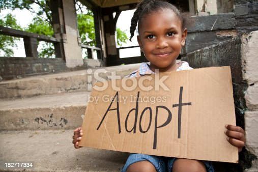 Little Girl Sitting and Holding Cardboard Sign Saying Adopt.See more from this series: