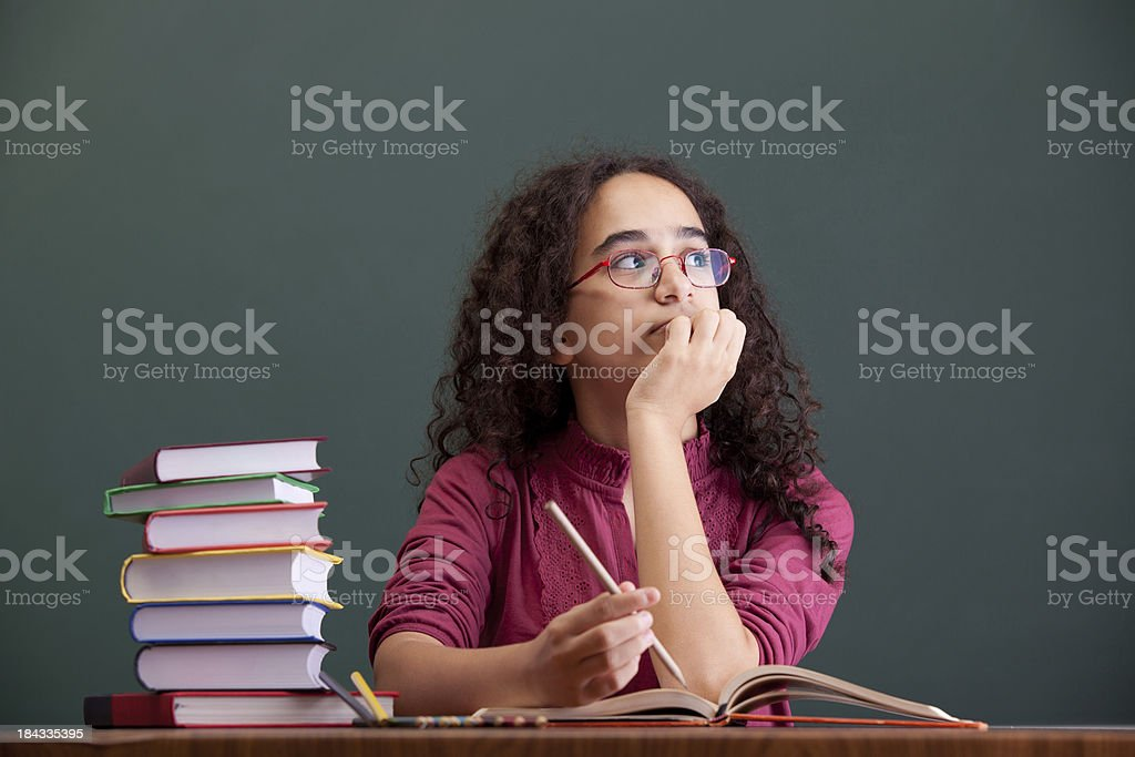 Little girl sitting and thinking before blackboard royalty-free stock photo