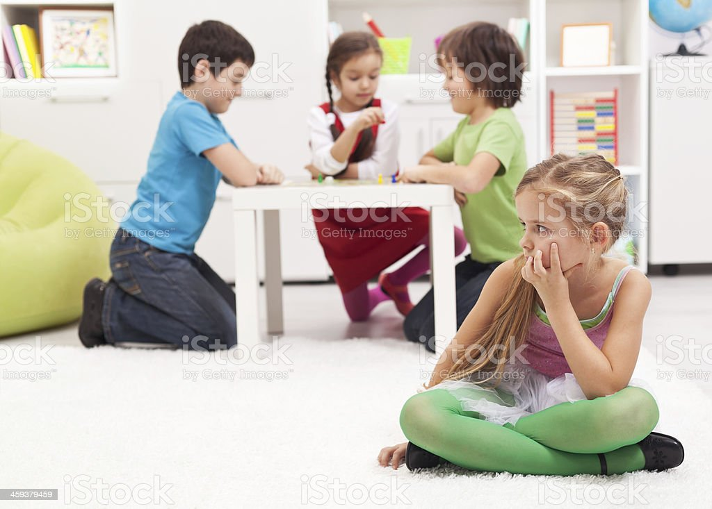 Little girl sitting apart - feeling excluded by the others stock photo
