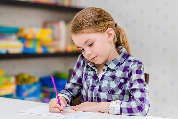 Kleines Mädchen sitzen am Tisch und Zeichnung Bleistift mit Lila – Foto