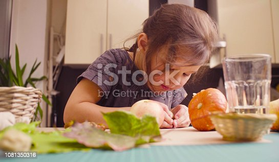 Autumn. Little girl sitting at the desk makes necklace of acorns