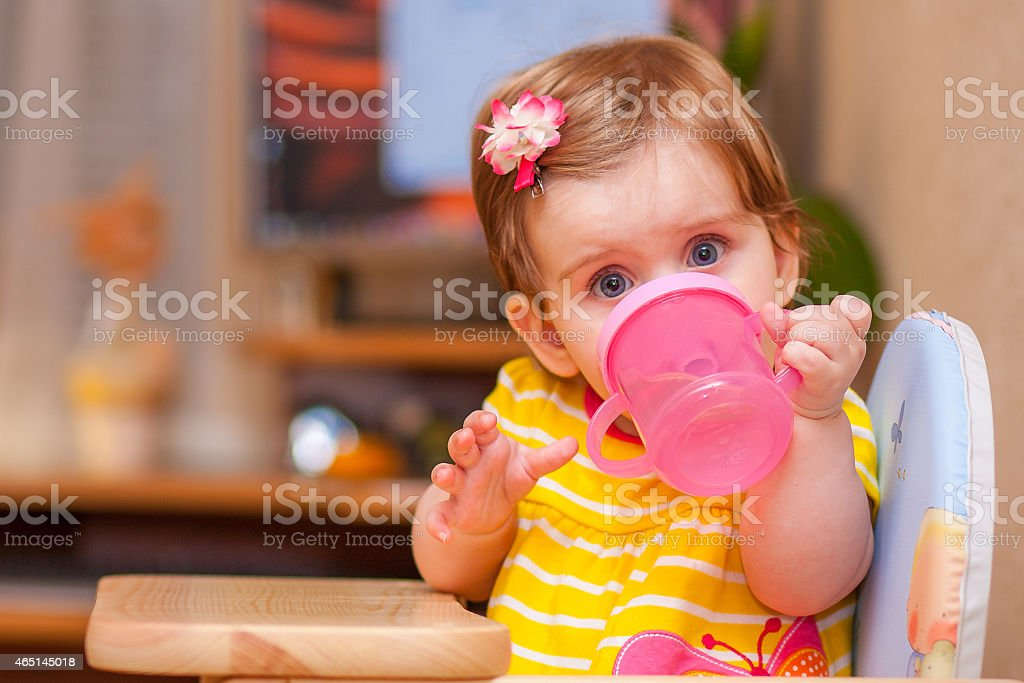 little girl sitting at the table. drink water. stock photo