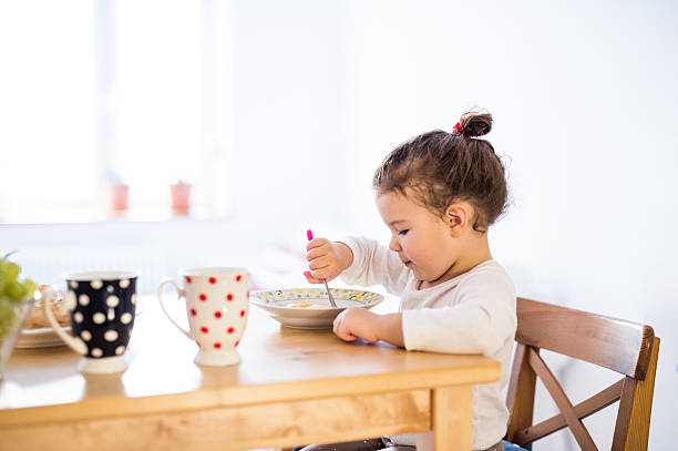 little girl sitting at the table, eating breakfast - kinderkueche holz stock-fotos und bilder