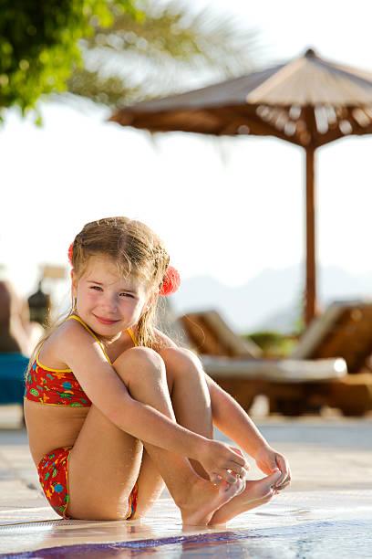 Kleines Mädchen sitzen von den Rand der Pool an einem sonnigen Tag – Foto