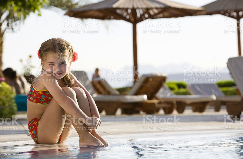 Little Girl Sitting By Edge of Pool on Sunny Day royalty-free stock photo
