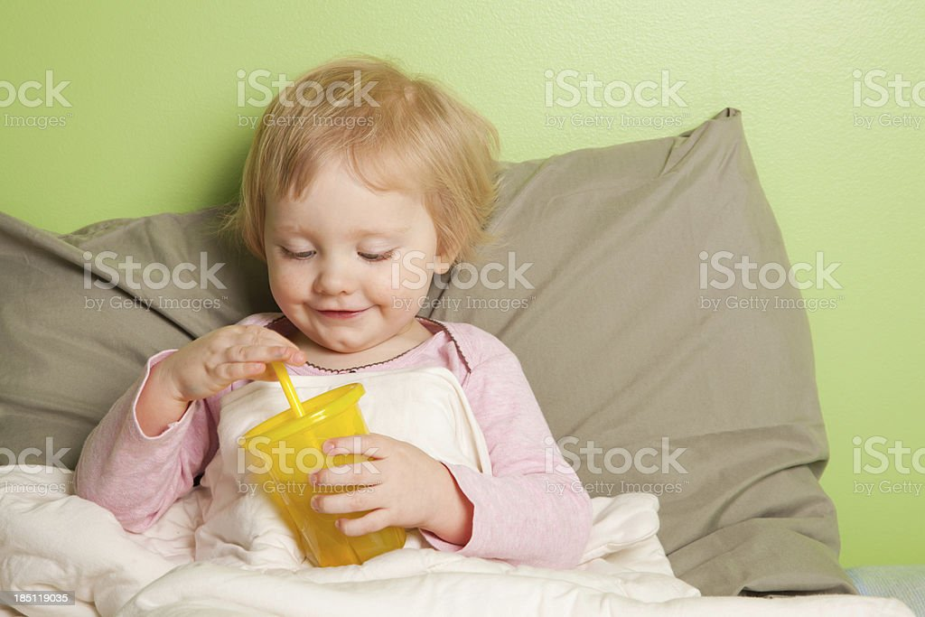 Little girl sitting in bed with drink royalty-free stock photo