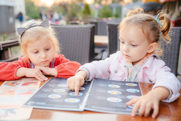 little girl sitting in cafe choosing food from menu lifestyle stock photo