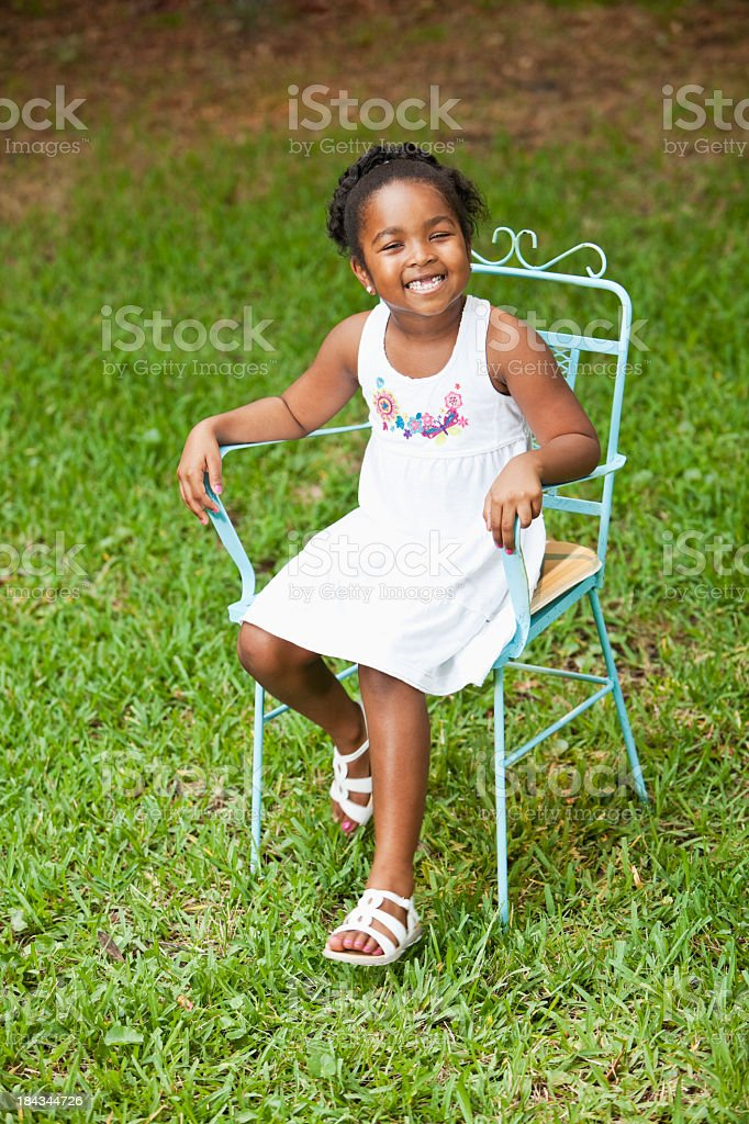 Little girl sitting in chair on grass stock photo