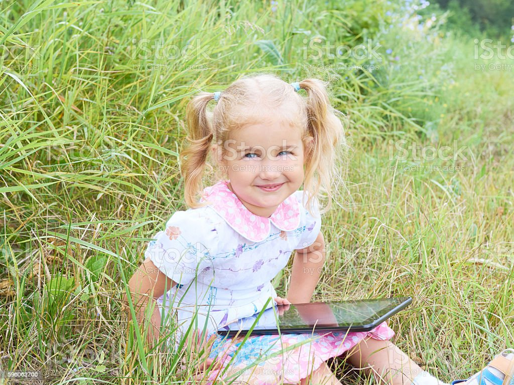 Little girl sitting in park on sunny day and play royalty-free stock photo