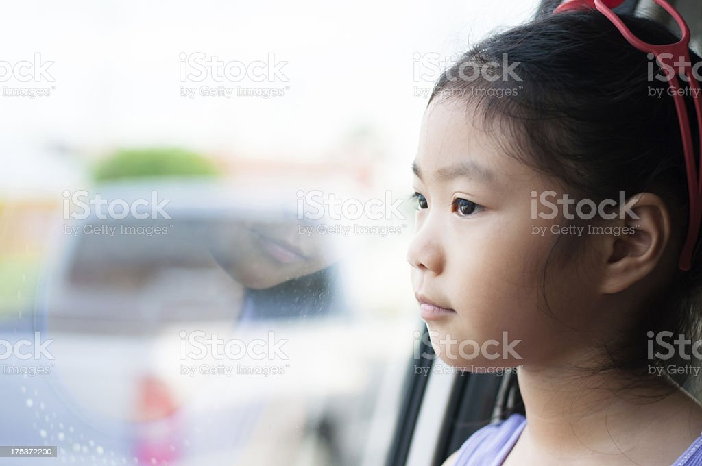 Little girl sitting in the car looking through window. royalty-free stock photo