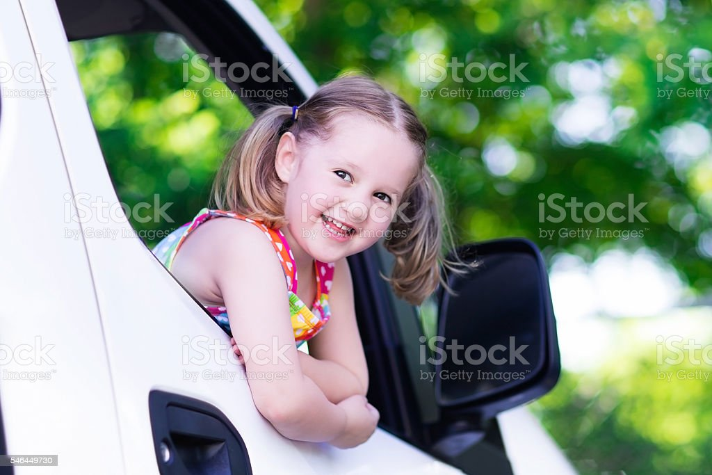 Little girl sitting in white car on summer day stock photo