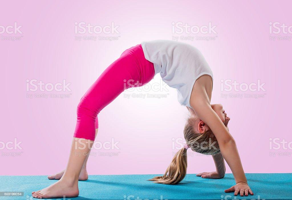 Little girl sitting in yoga pose stock photo