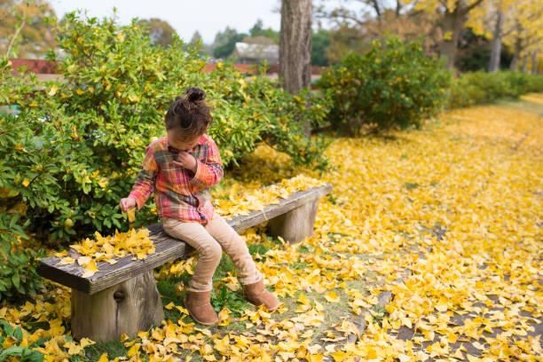 kleines mädchen sitzt auf einem park bench - lammfellstiefel stock-fotos und bilder