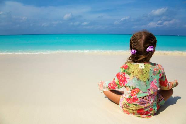 Kleines Mädchen sitzt am Strand – Foto