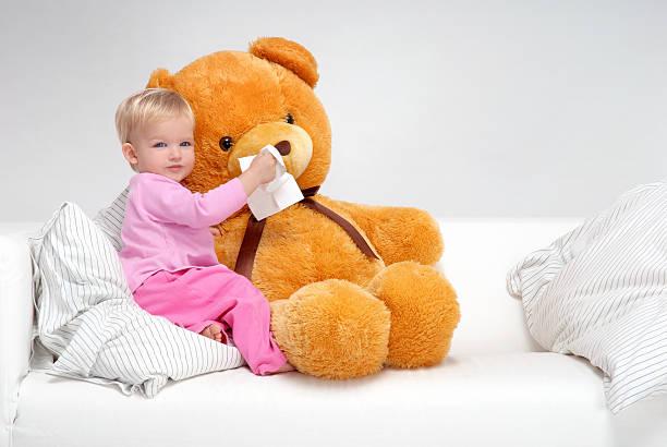 Kleines Mädchen sitzt auf dem Bett und Wirtschaftshilfe Teddy's Nose – Foto