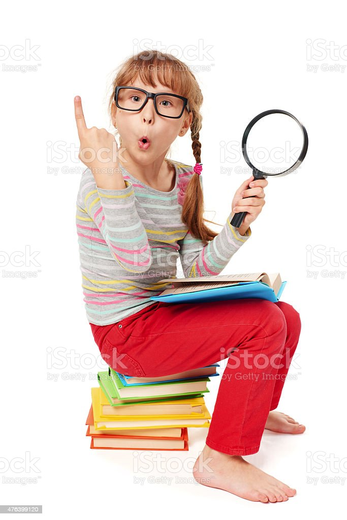 Little girl sitting on floor with a lot of books stock photo
