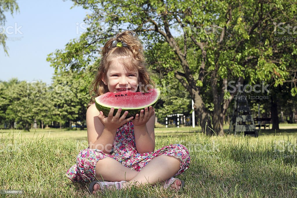 little girl sitting on grass and eat watermelon royalty-free stock photo