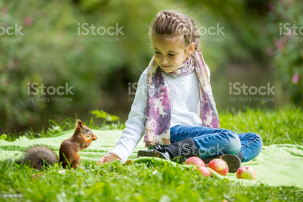 Little girl sitting on green lawn and feeding squirrel stock photo