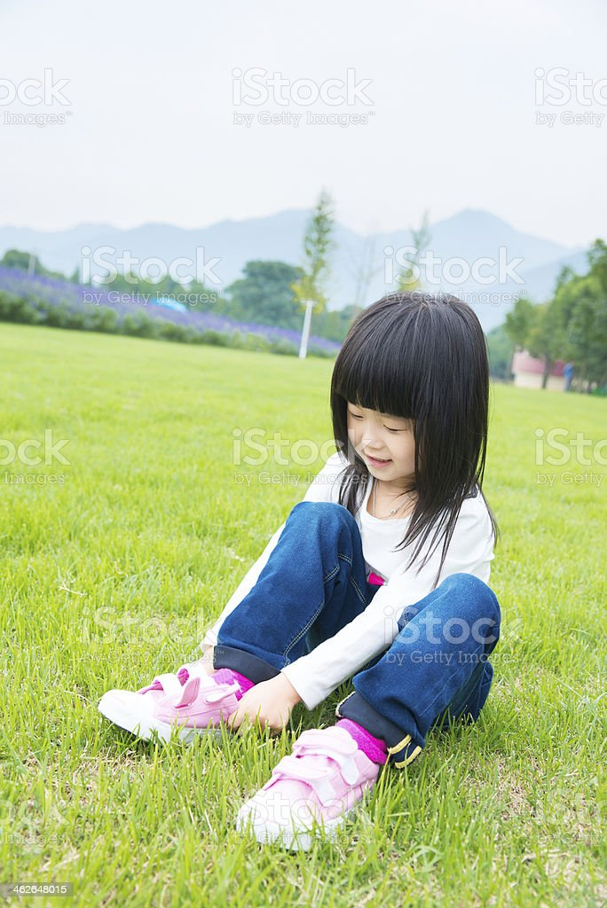 Little girl sitting on meadow,lace up shoes royalty-free stock photo